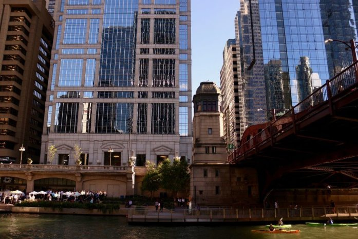 Kayakers paddle under a bridge in downtown Chicago; skyscrapers glisten in the sun behind them. ©KettiWilhelm2019