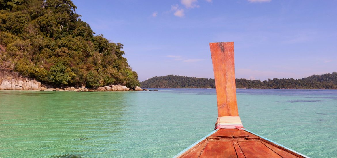 The view of steep cliffs and turquoise waters from the front of a long tail boat in Thailand. ©KettiWilhelm2019