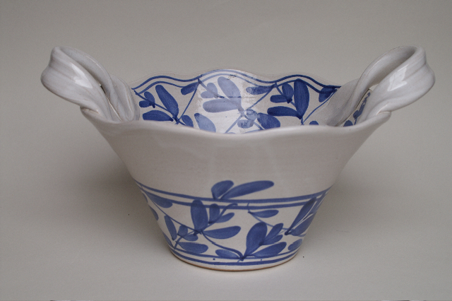 A small bowl with wide rim and handles, decorated with blue flowers.