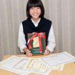 英語弁論大会での盾と賞状を手にする中学生の女の子