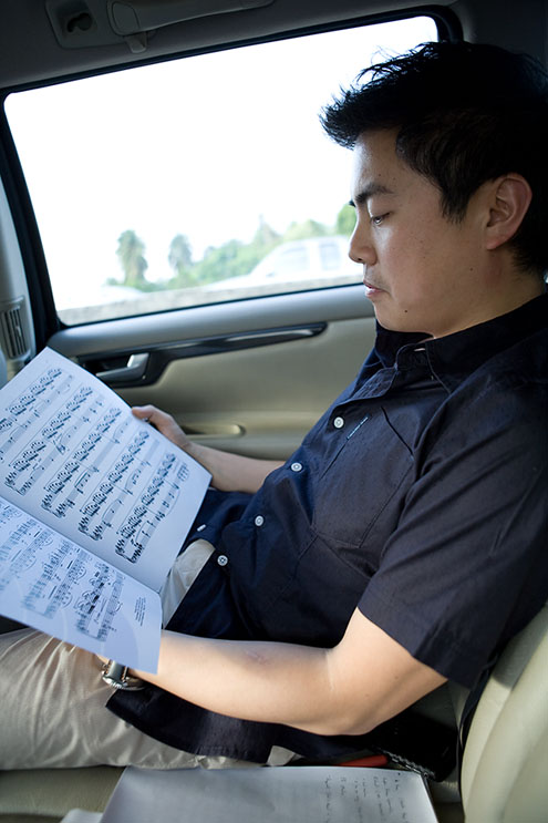 Tan reviewing the music in the car on the way to rehearse with the orchestra.
