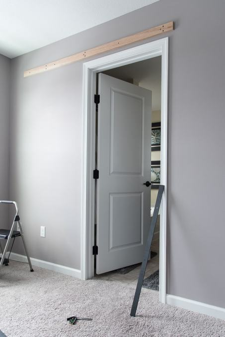 How to build a modern barn door for your home. Step by step instructions for building a craftsman style door and installing a barn door hardware kit.
