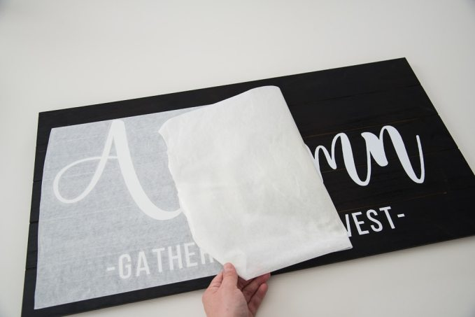 Peeling off transfer tape from a wooden pallet with a white vinyl design