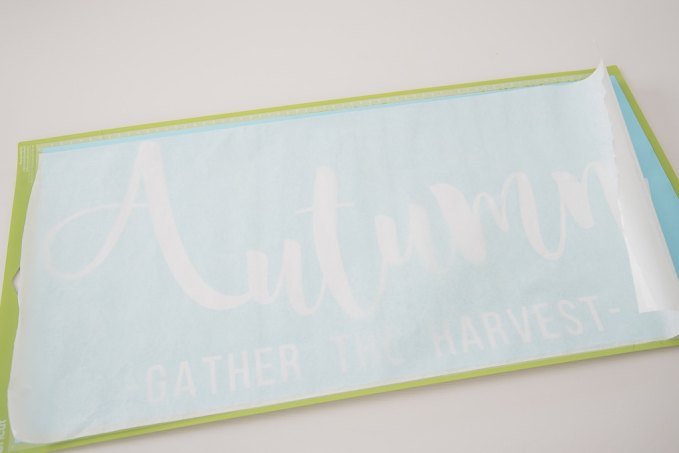 Cricut cutting mat with white vinyl Autumn design and transfer tape over the top