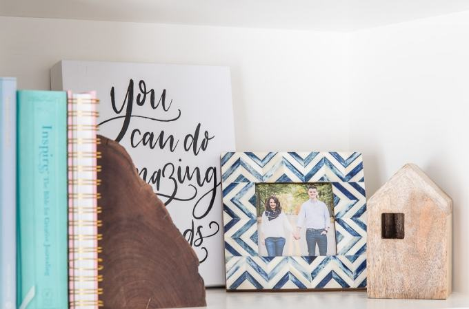 blue picture frame and wooden house on a shelf