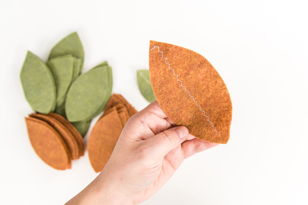 close up of felt tan leaf with stitch down the center