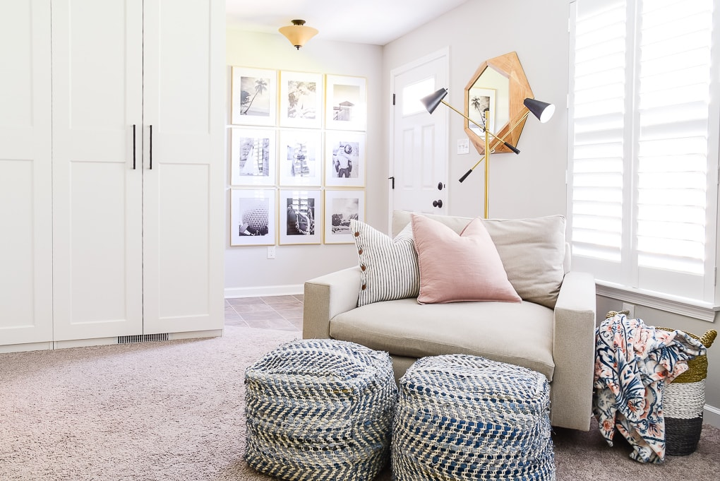 west elm harmony chair blue poufs and gold gallery wall in basement office room