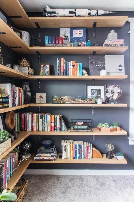 floating industrial shelves with decorations and books in modern masculine home office