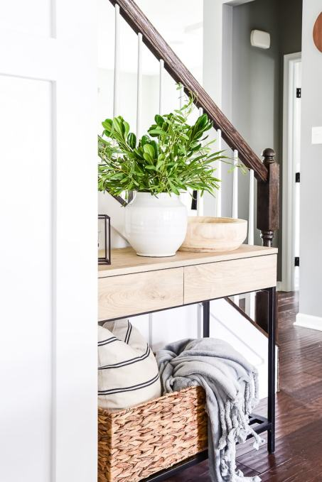 console table with basket of pillow and blanket and decorations on top with greenery vase