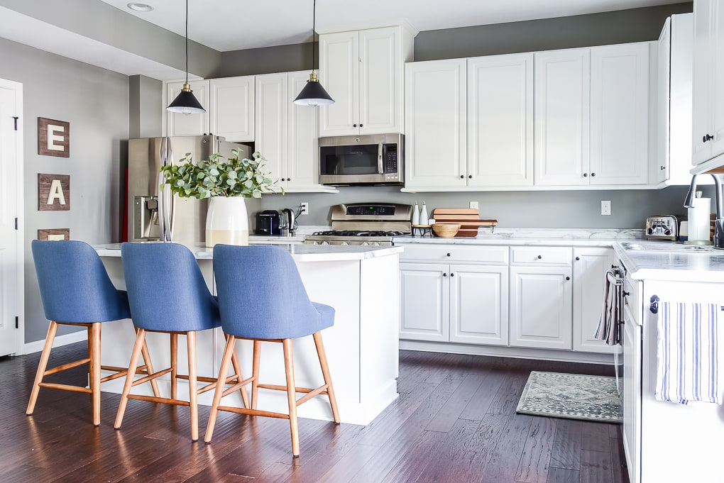 white kitchen with blue barstools brown floors and modern decor