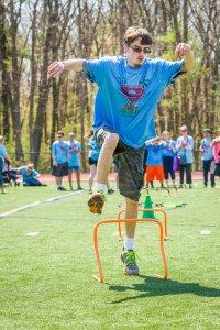 Student jumping hurdle.