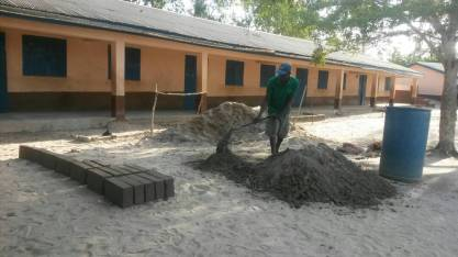 Master Mason, Ben Ntasese, mixing cement to repair the school building