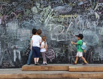 children doing chalk graffitti on a wall