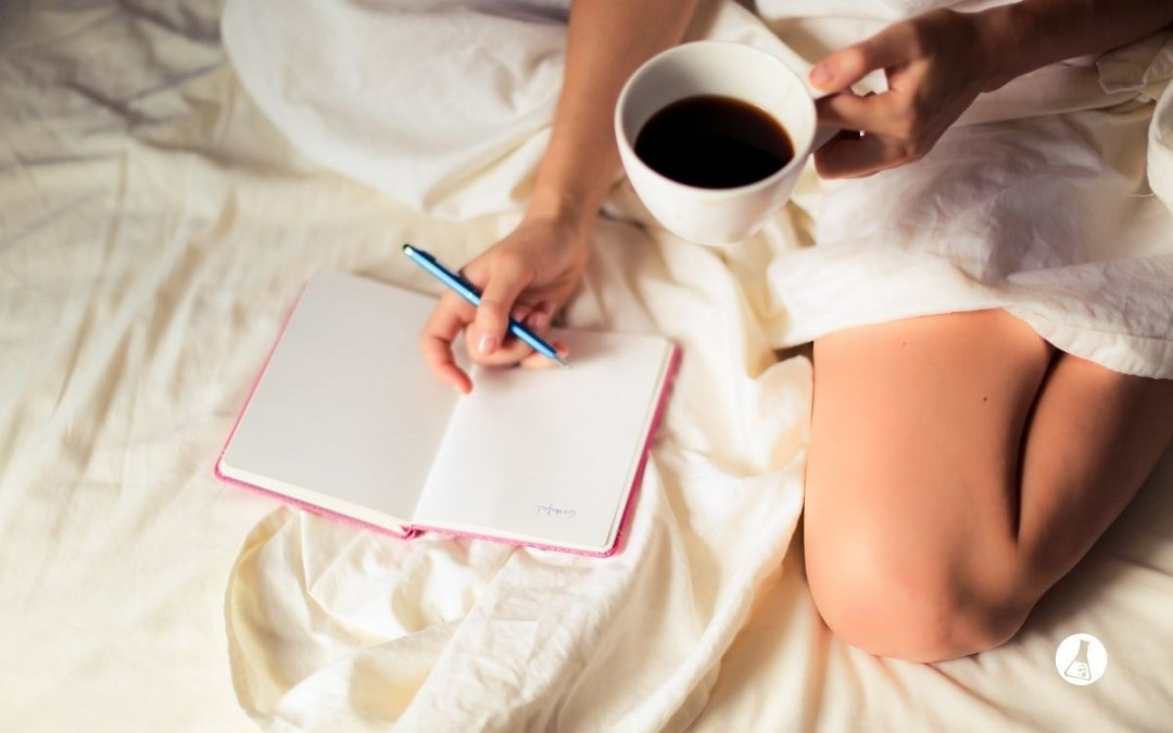 A woman building new habits discovering what's keeping her stuck and holding a coffee while writing in her journal