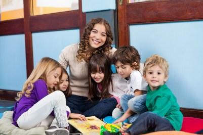 Happy teacher sitting with children on floor in classroom