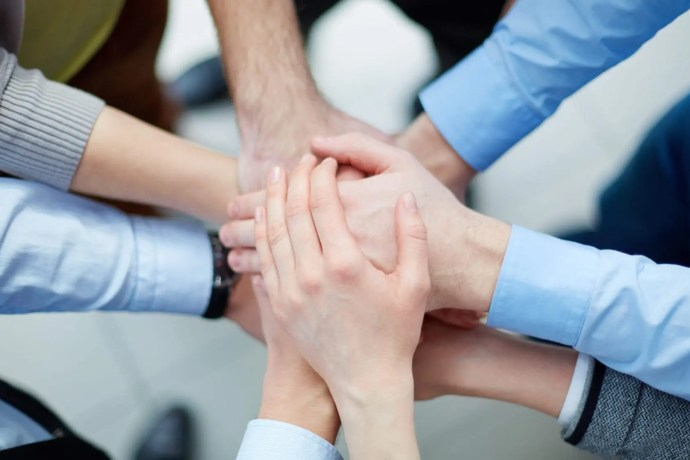 Above view of business partners making a pile of hands