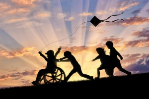 Happy boy in wheelchair playing with children and kite sunset.