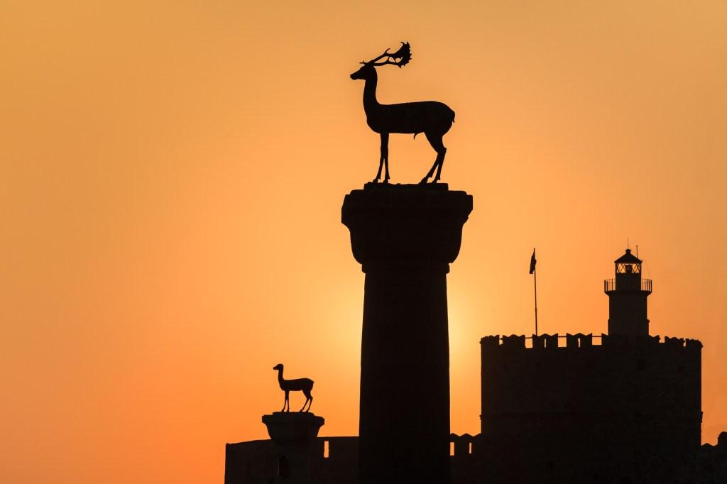 sunrise in Mandraki harbor. Rhodes, Greece 2 deers