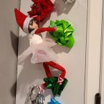 Elf on the shelf climbing up bows