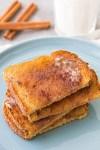 Homemade cinnamon sugar toast stacked on a plate.