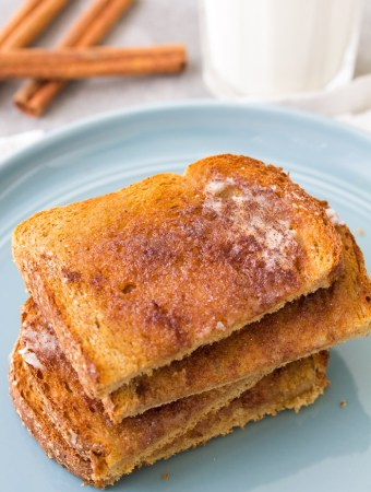 Homemade cinnamon sugar toast stacked on a plate.
