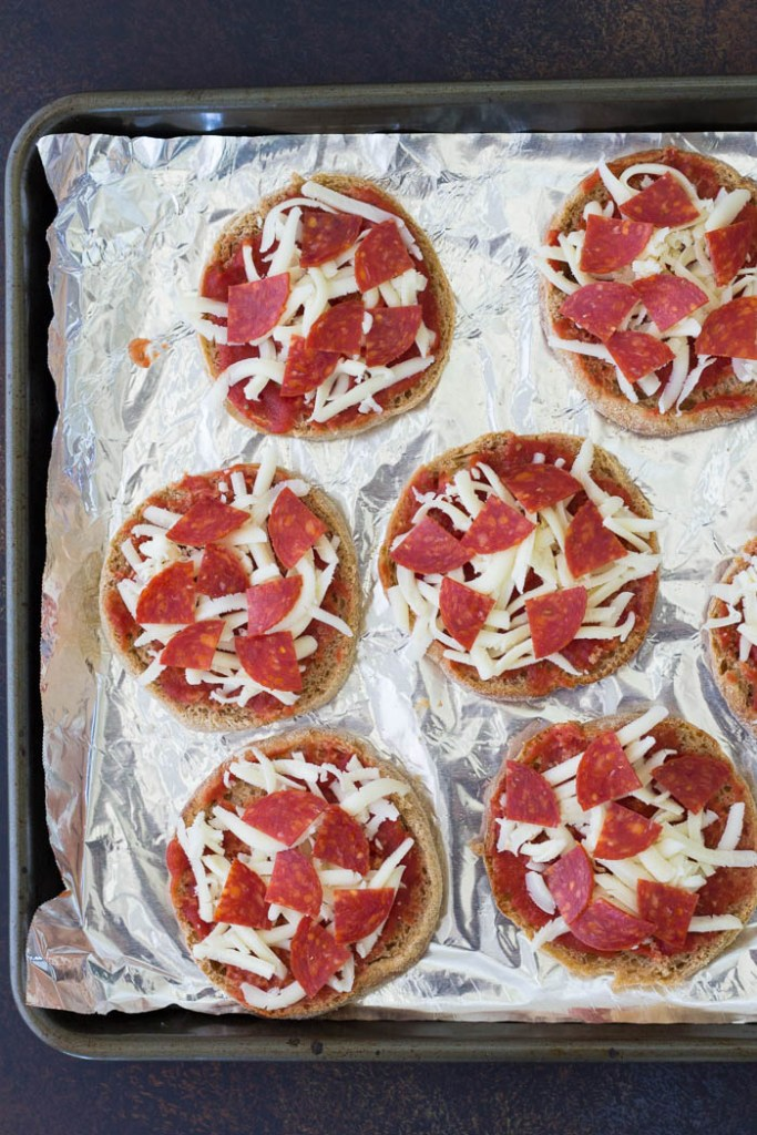 English muffin pizzas with cheese and pepperoni, before baking.