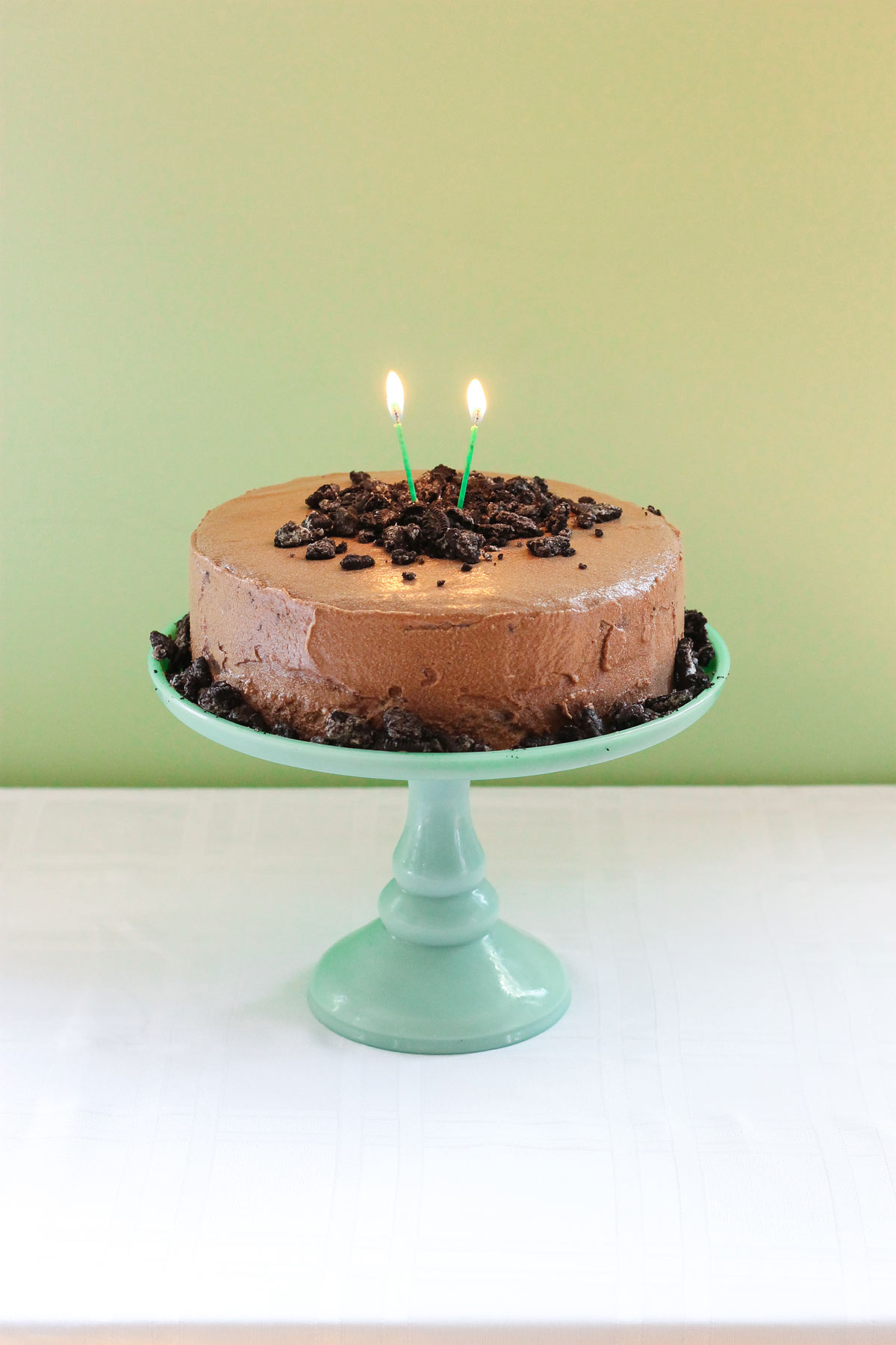 Mocha cake with mocha frosting with candles on a green cake platter