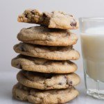 chocolate chip cookies piled up next to milk