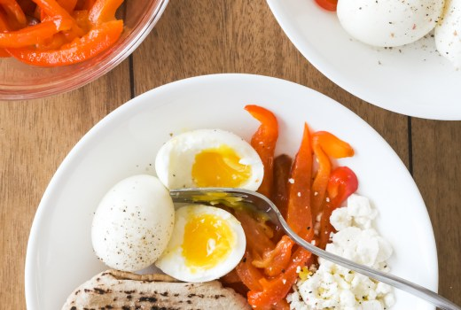 roasted red peppers in a bowl with soft boiled eggs cheese and pita