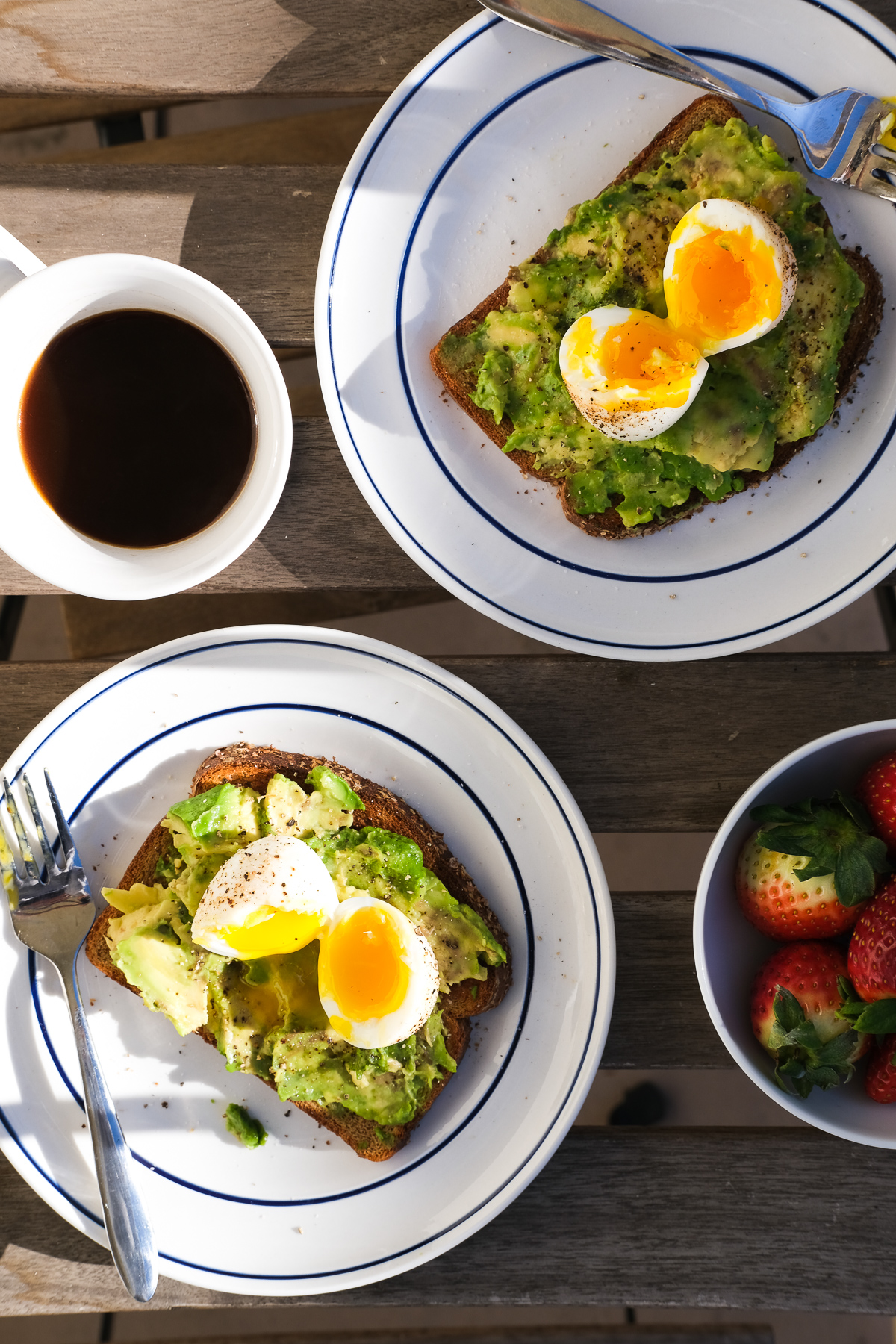 plates of avocado toast with soft boiled eggs and strawberries for breakfast