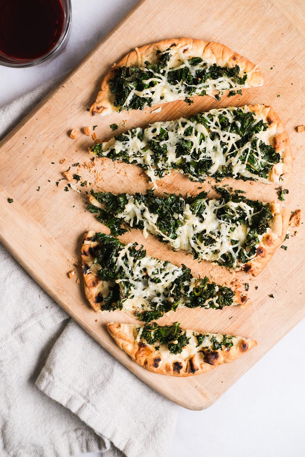 kale parmesan flatbread pizza cut up on a cutting board