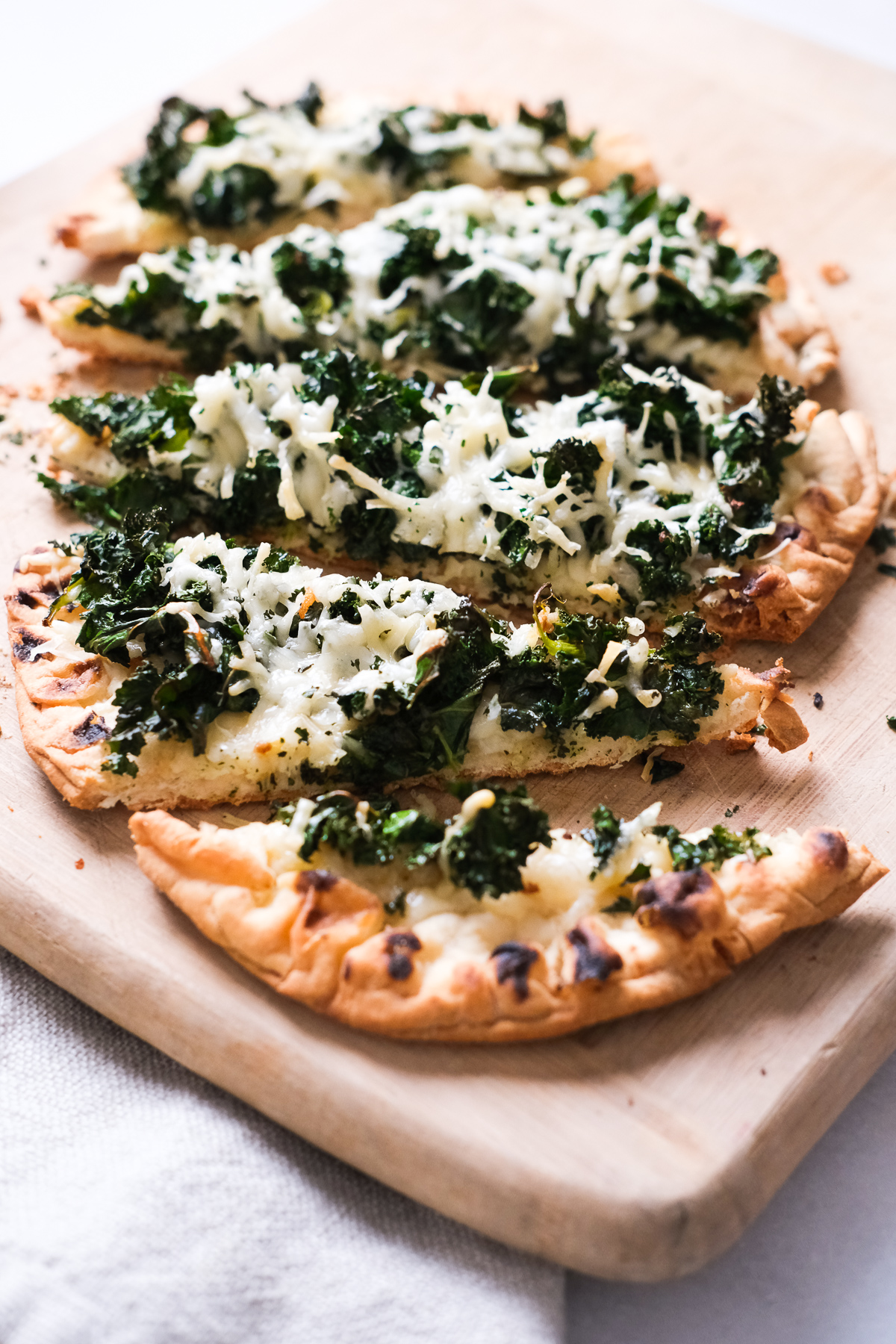 close up of kale parmesan flatbread slices on a cutting board