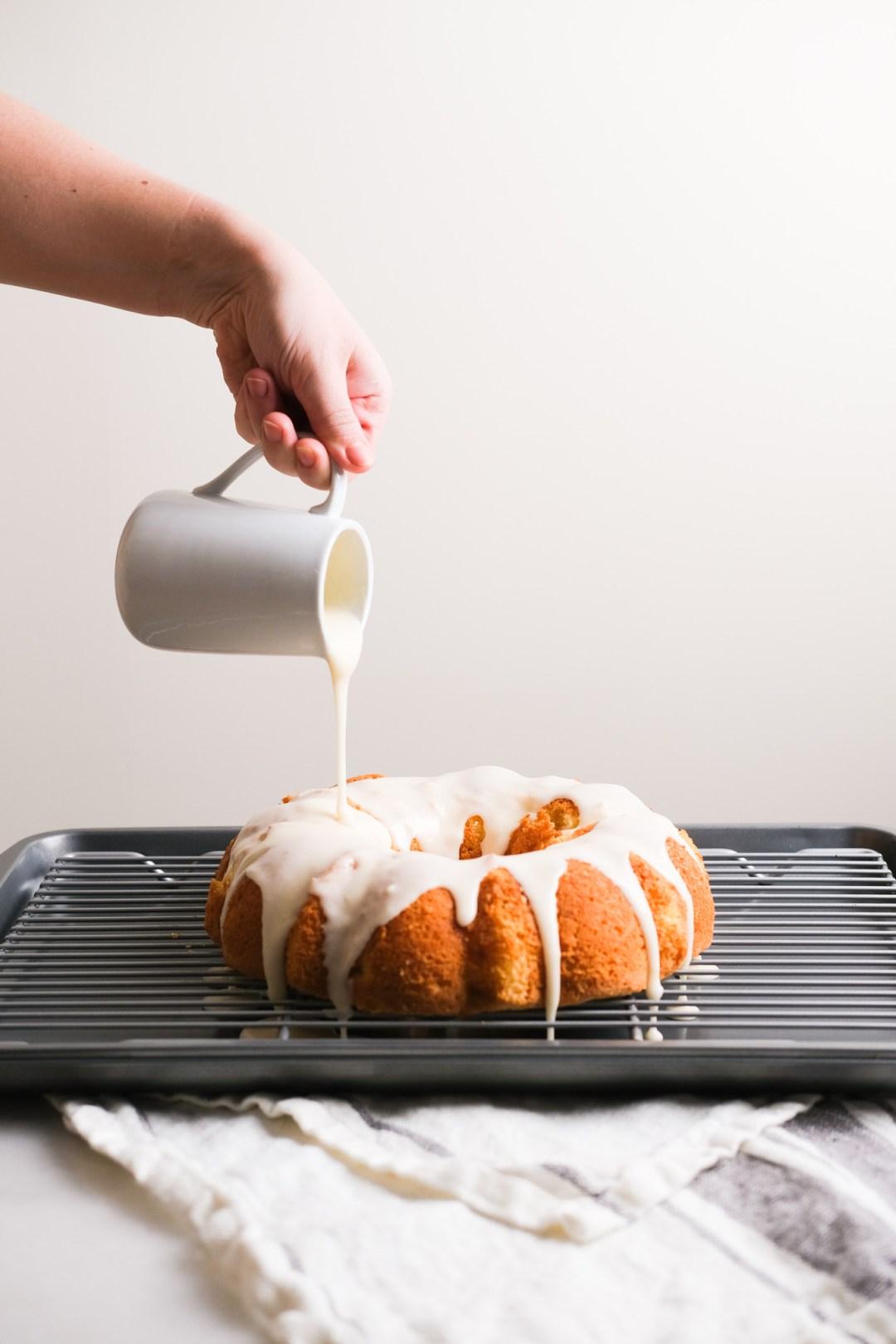 pouring vanilla frosting on lemon cake