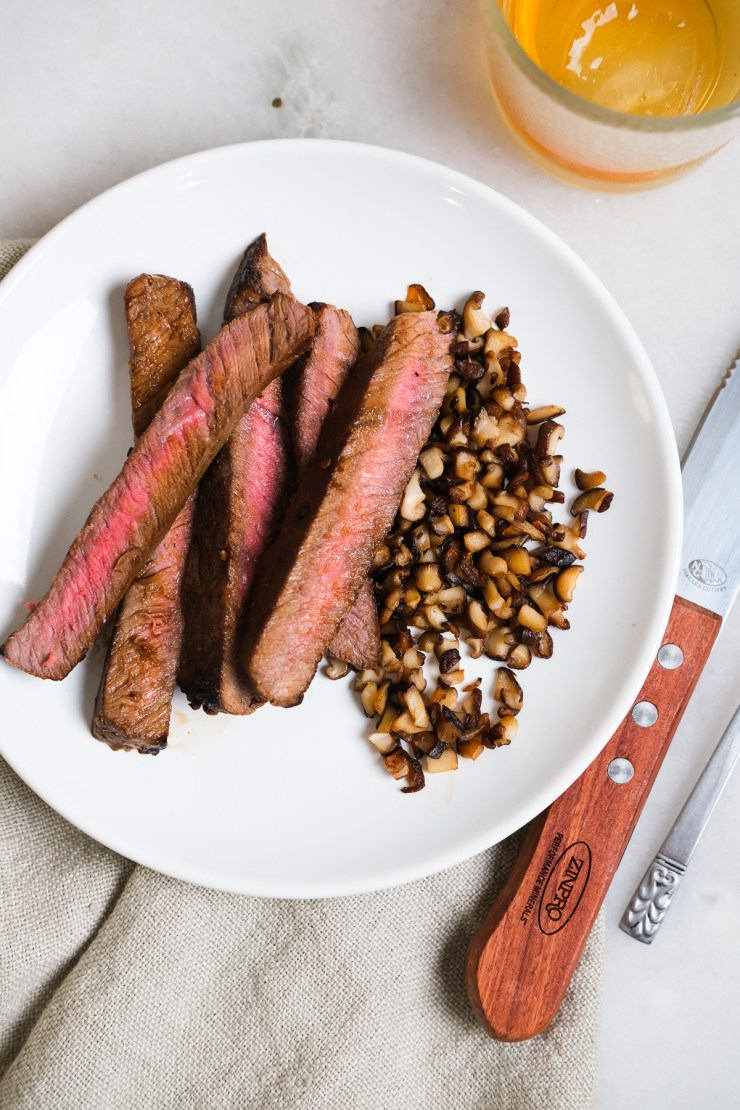london broil strips on a plate with shiitake mushrooms