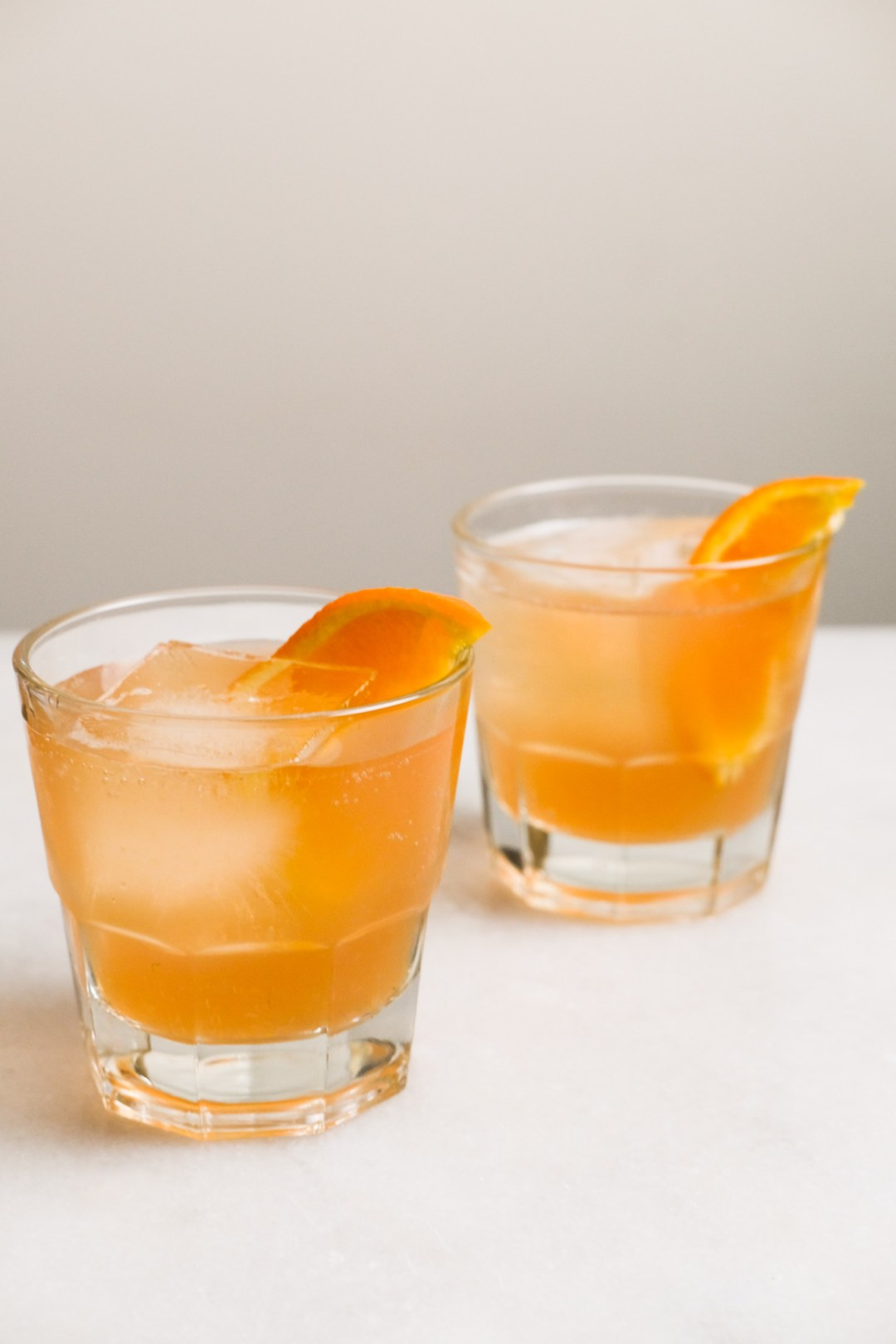 two glasses of orange cranberry bourbon cocktails