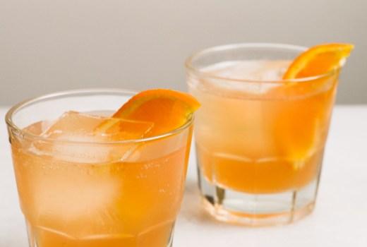 two glasses of orange cranberry bourbon cocktails