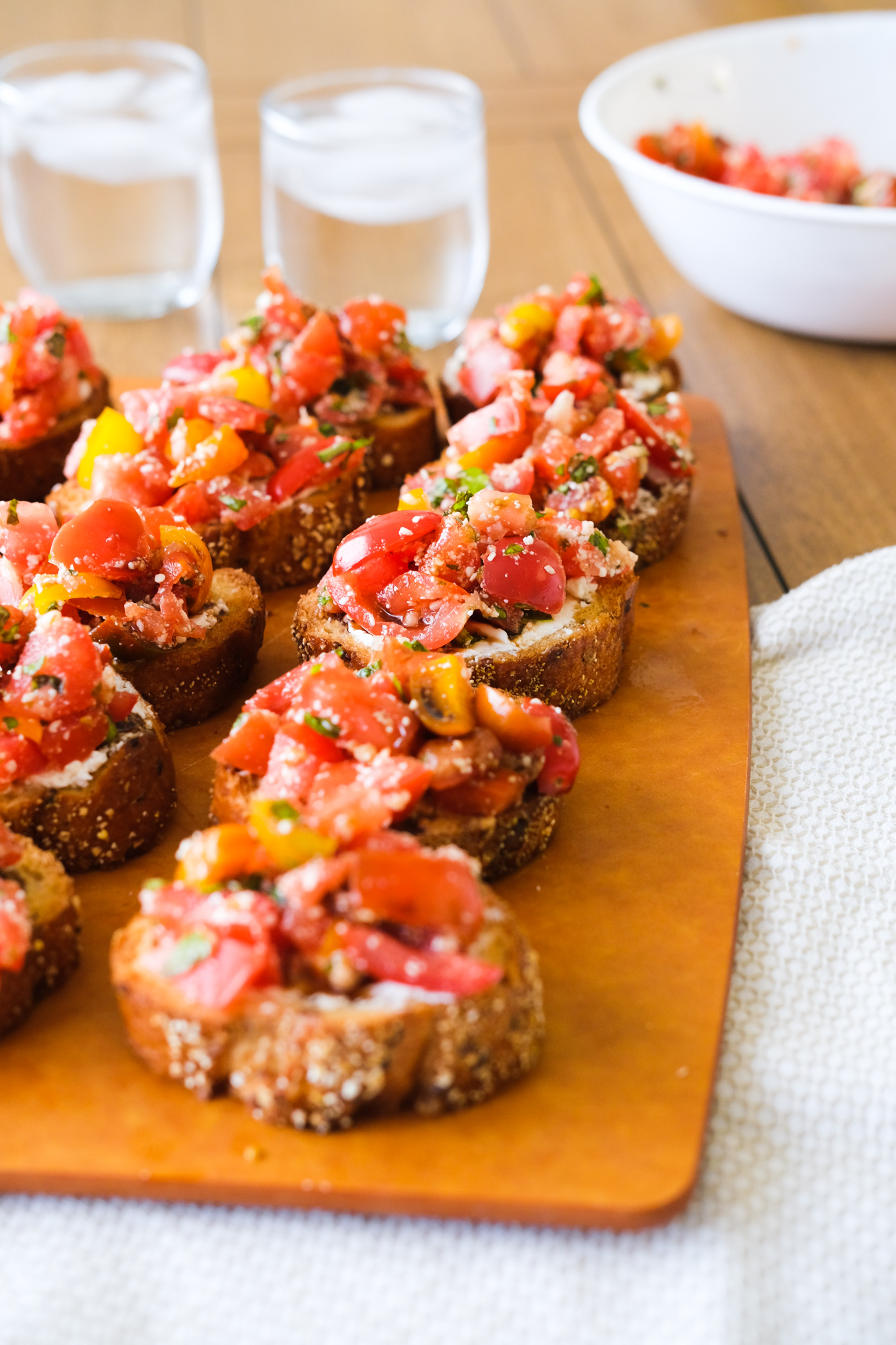 bruschetta on a cutting board with glasses of water