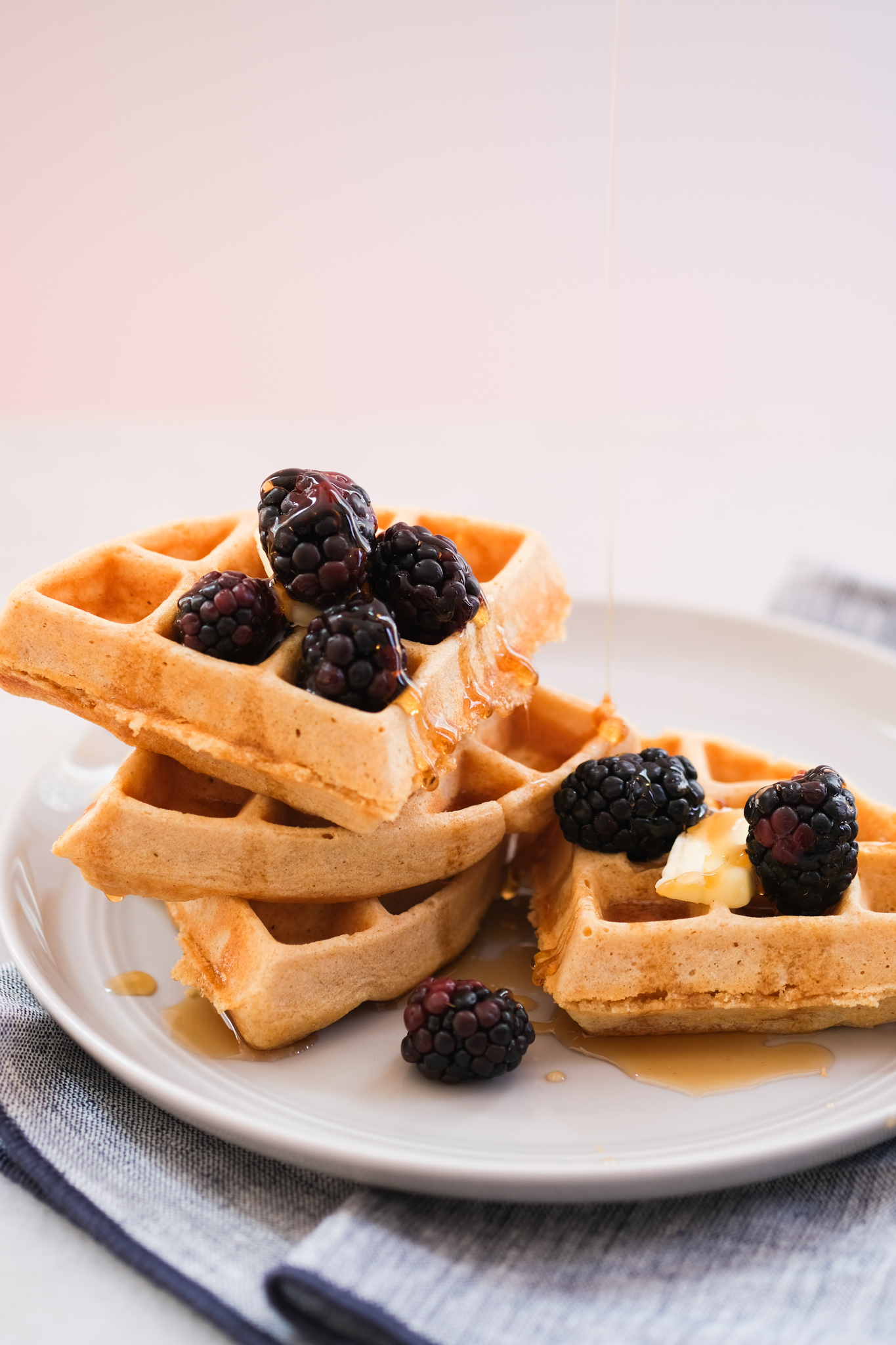 whole wheat waffles with blackberries and syrup drizzled on top
