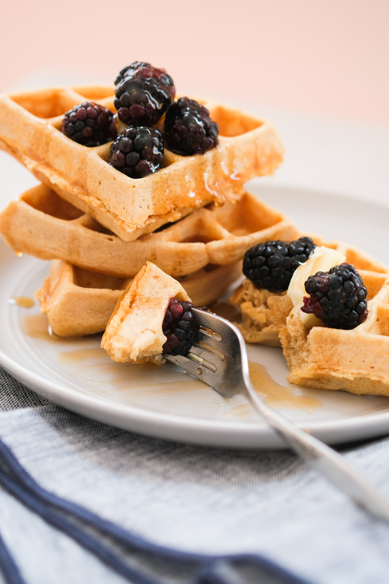 biting into a whole wheat waffle with blackberries
