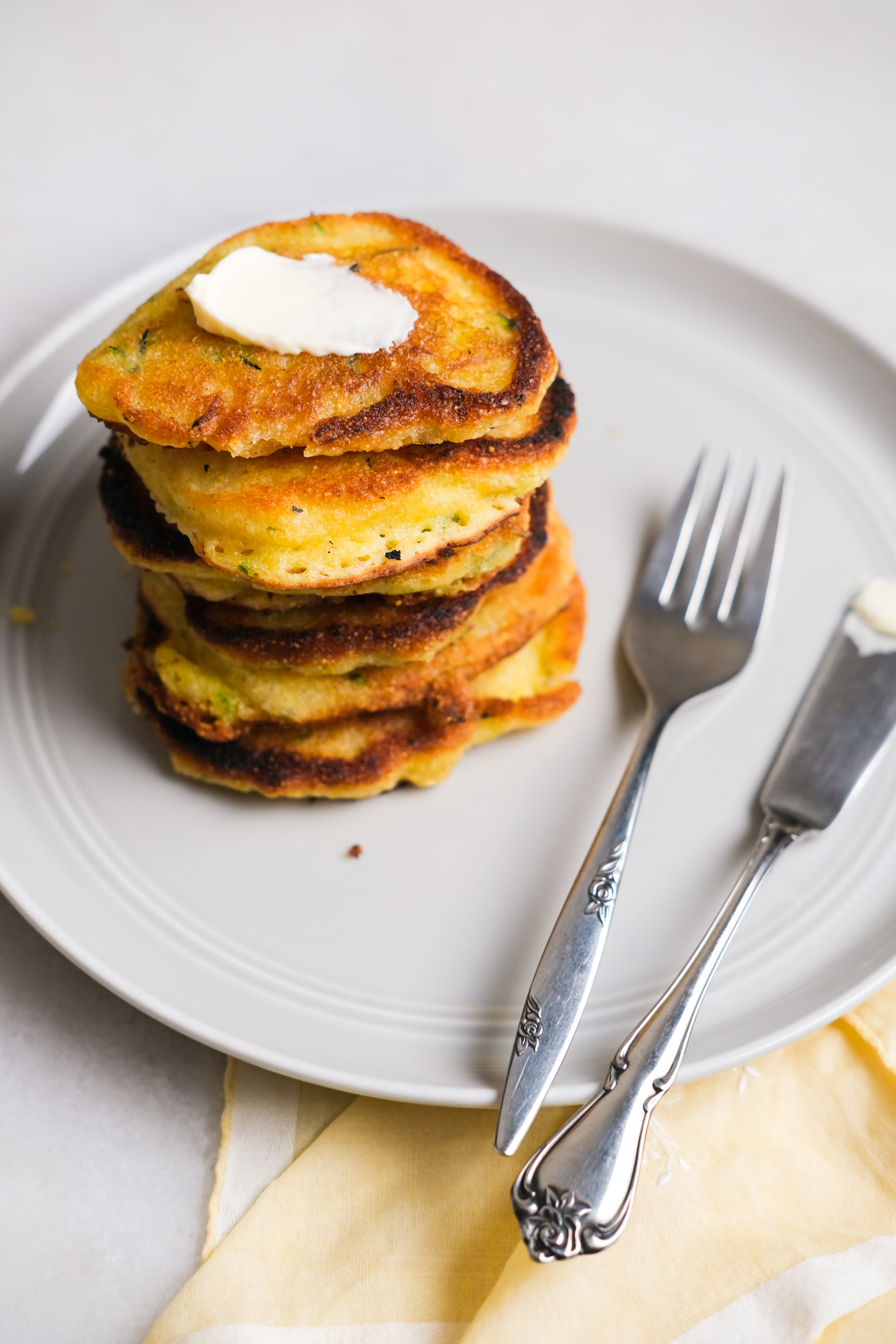zucchini fritters stacked on a plate with spreadable butter
