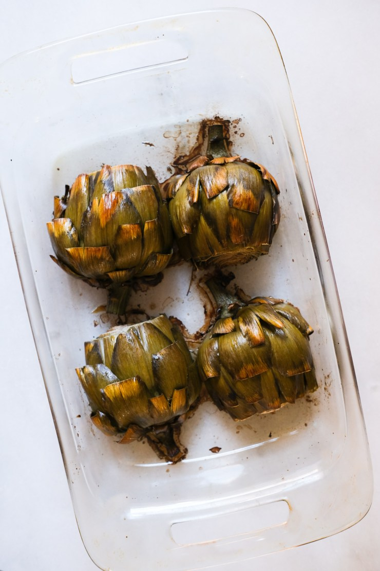 roasted artichokes in a glass dish