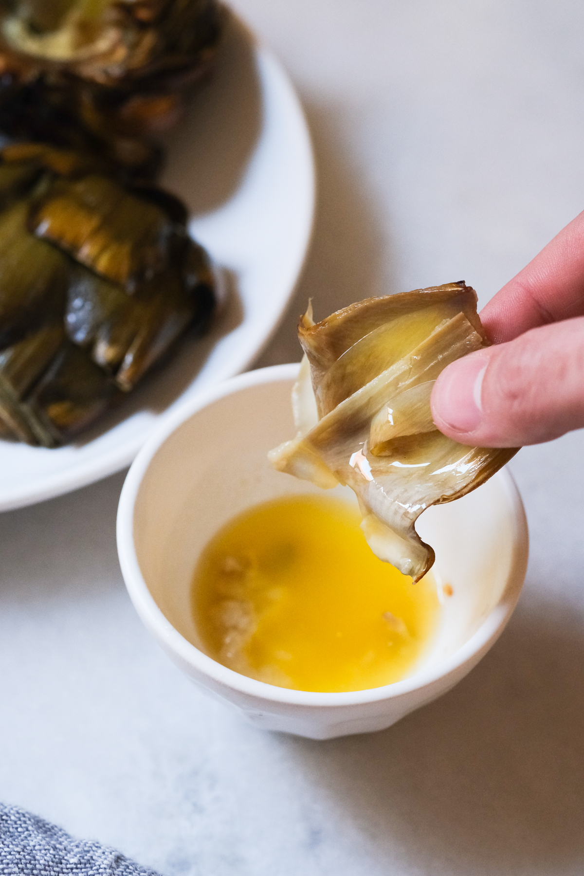 dipping artichoke leave in garlic butter