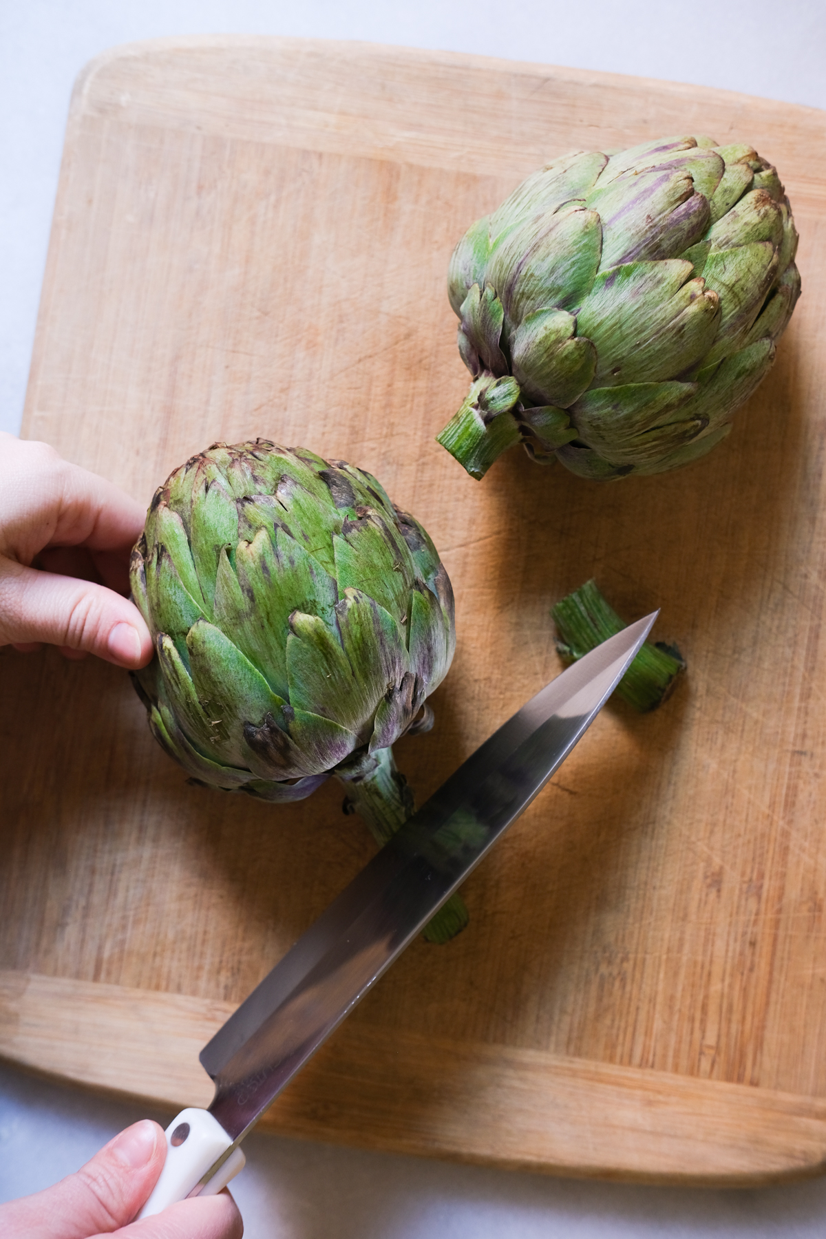 chopping the stem off an artichoke