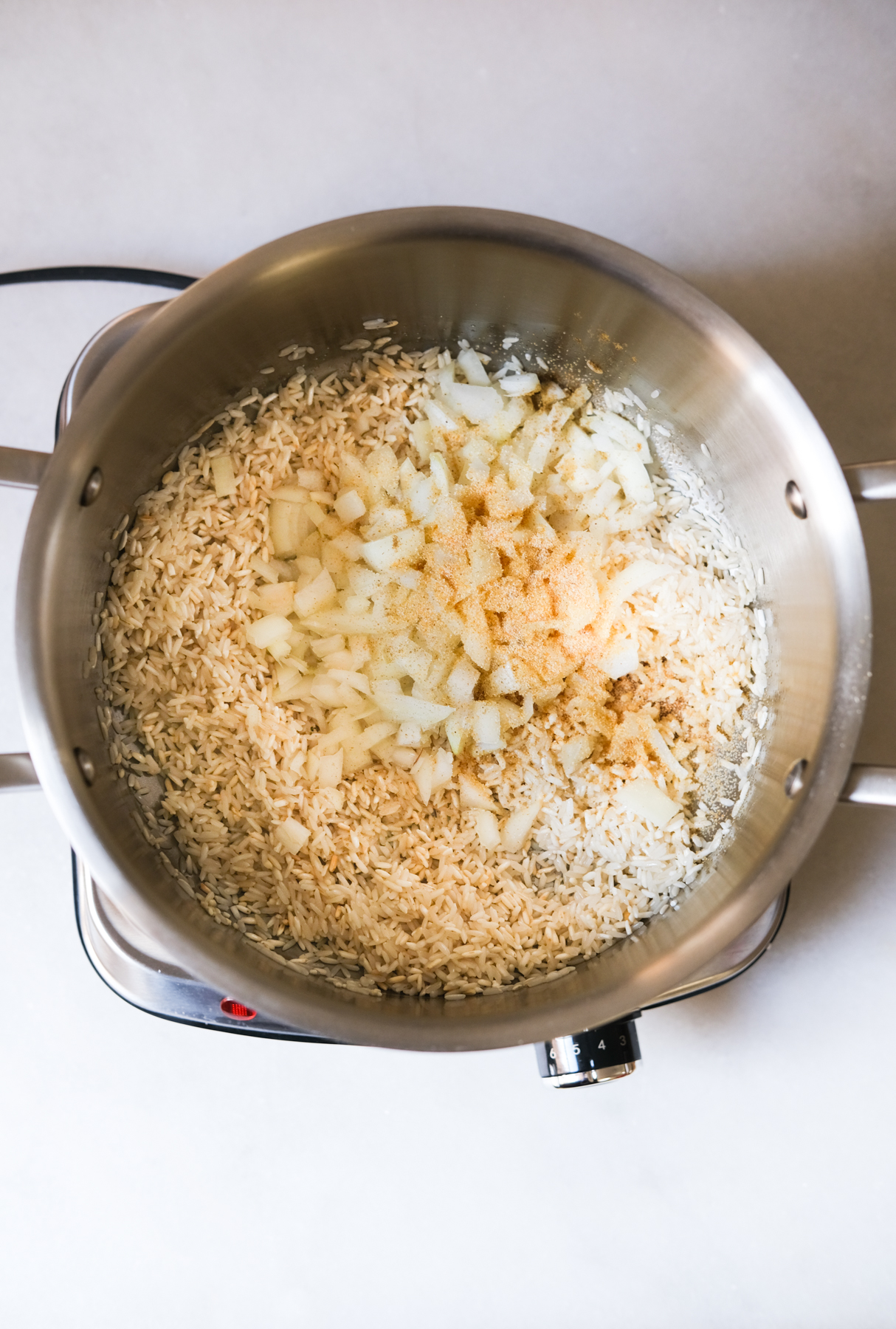 adding in onions and seasoning with pre-cooked rice for Mexican rice
