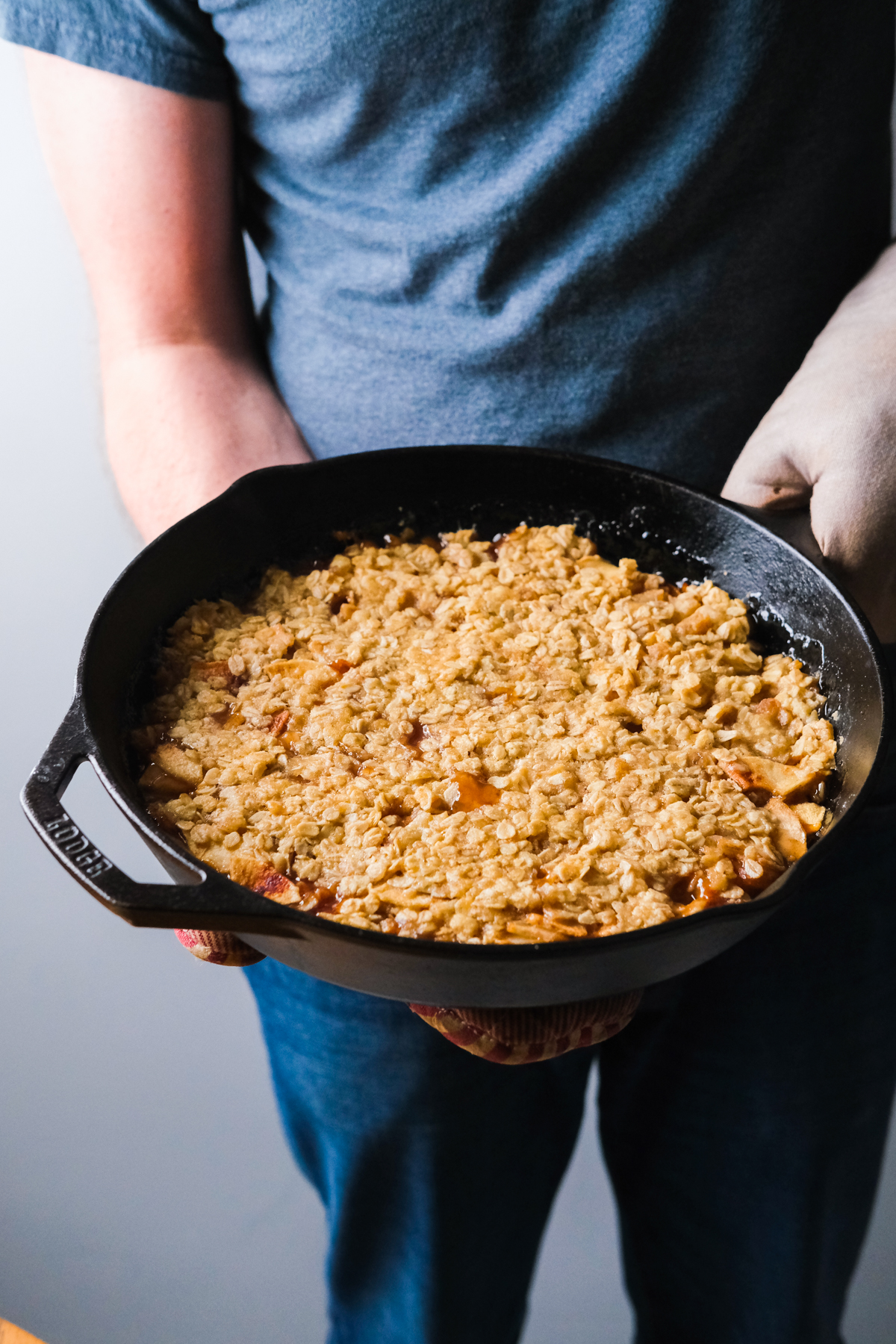 holding a cast iron skillet with apple pear crisp