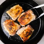 flipping chicken thighs in a cast iron skillet with tongs