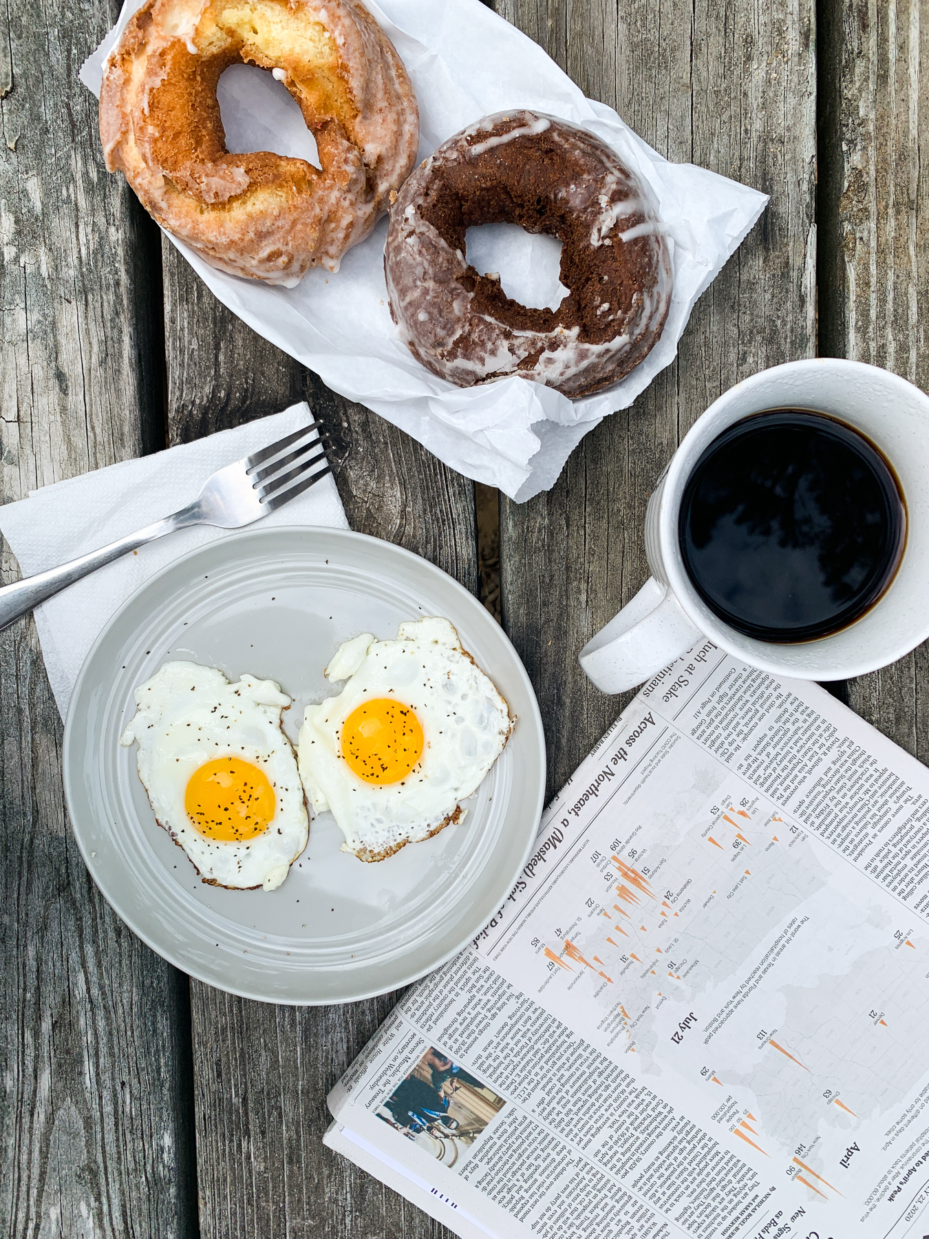 fresh baked donuts with fried eggs on a picnic table with coffee