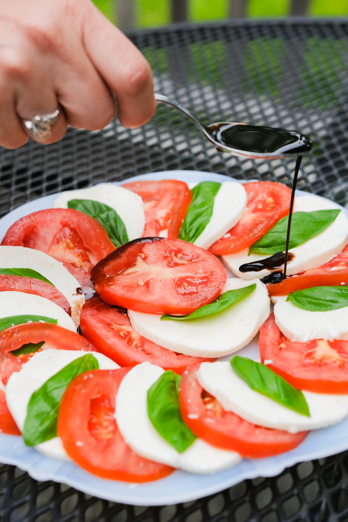 drizzling balsamic on caprese salad