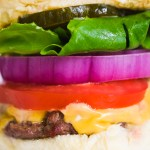 close up of a cheeseburger with tomato onion lettuce and pickles