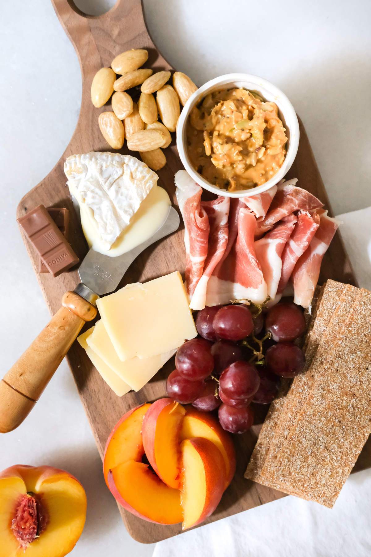 mini charcuterie board with cheese meat fruit chocolate and nuts